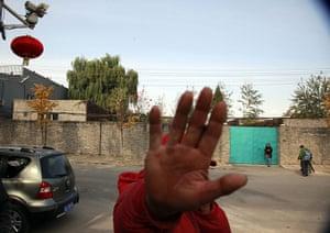 Ai Weiwei: A worker pretends to obstruct a photographer
