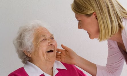 Young blond caring woman affectionately greets laughing grey haired senior old age retired pensioner