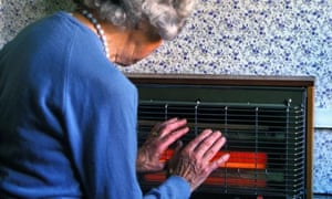 A pensioner warms hands on electric fire