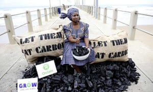 Oxfam activist pretends to eat coal in a protest outside the Durban talks