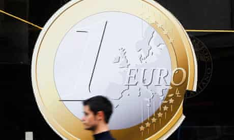 Man walks past a sign showing a euro coin