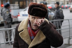 Moscow protests: A man scratches his eye, with Interior Ministry officers standing guard