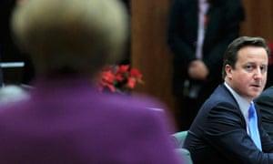 David Cameron looks at Angela Merkel