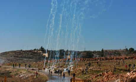 Palestinians try to avoid teargas fired by Israeli soldiers in Nabi Saleh