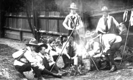 Boy Scouts sitting around a camp fire 1910