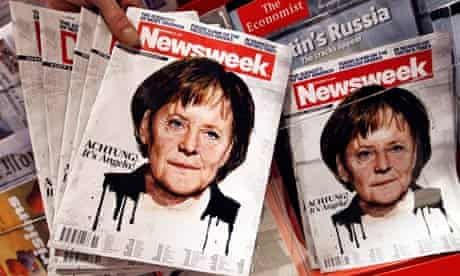 Copies of a Newsweek magazine bearing a picture of German Chancellor Angela Merkel