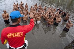 Indonesia punks: A police officer gives instruction to a group of punks in a lake