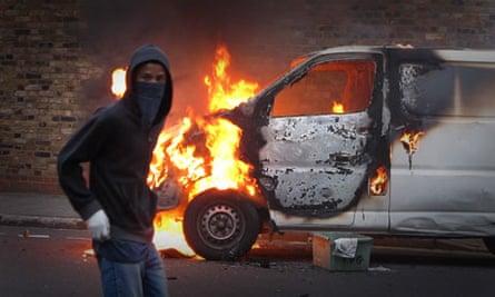 A young man walks past a burning car