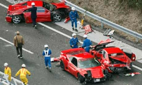 Police officers investigate wrecked luxury cars at the site of a traffic accident