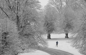 UK Weather: A man runs in the snow at Lyme Park near Manchester
