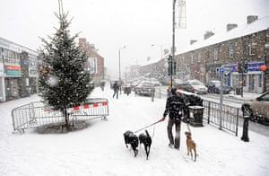UK Weather: People walk through snow in Main Street, Gateshead