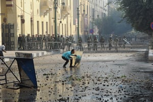 Tahrir Square clashes: An Egyptian protester takes cover during clashes