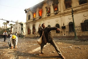 Tahrir Square clashes: A protestor hurls stones during clashes with security forces
