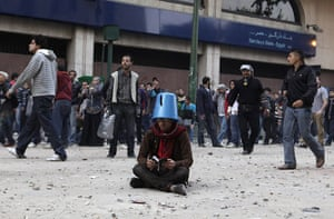 Tahrir Square clashes: A protester shields himself with a bucket while reading the Qur'an