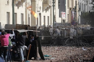 Cairo clashes: Egyptians take cover throwing a fire bomb toward army soldiers