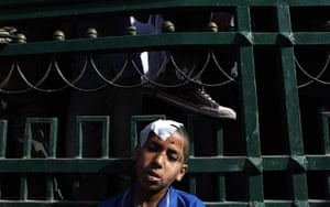 Cairo clashes: An injured Egyptian youth protester rests after getting first aid care