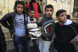 Cairo clashes: Egyptian boy holds a burnt manuscript after the Institute of Egypt burned