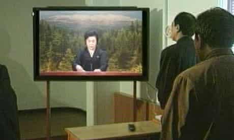 North Korean officials watch a news broadcast announcing death of North Korean leader Kim Jong-il