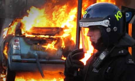 A police officer in riot gear stands near a burning car in Hackney, London