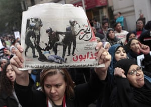 women protest in cairo: A woman raises a copy of Al Tahrir newspaper