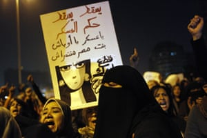 women protest in cairo: A protester carries a poster
