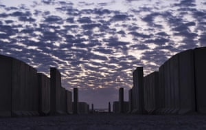 FTA: Lucas Jackson: The sun rises behind an alleyway lined with blast walls inside Camp Adde