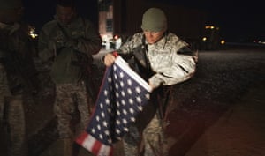 FTA: Lucas Jackson: A soldier folds up a US flag before leaving Camp Adder