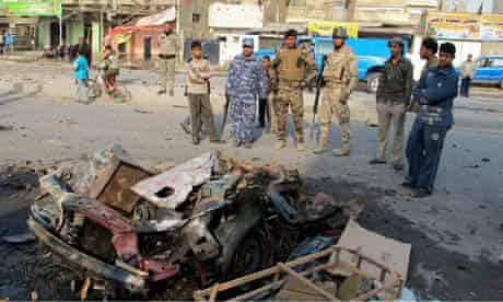 Iraqi security forces inspect the site of the bomb attack in Baghdad