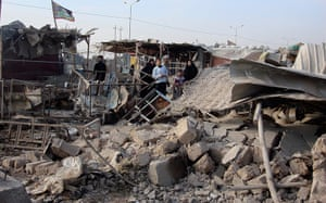 Iraq bombing: Residents gather at the site of a bomb attack in Baghdad's Shula district
