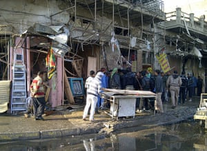 Iraq bombing: Residents gather at the site of a bomb attack in Alawi district