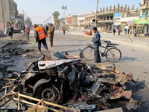 Iraq bombing: A boy stands near the site of a car bomb attack in Baghdad's Shaab District