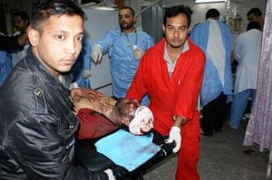 Iraq bombing: Workers carry a wounded man after a bomb attack at a hospital in Baghdad