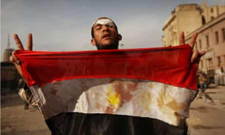 An anti-government protestor holds a bloodied Egyptian flag in Tahrir Square, Cairo.