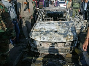 Damascus Suicide Bombing: Syrian security members inspect the wreckage of a car