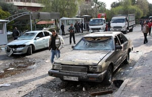 Damascus Suicide Bombing: A man inspects a damaged vehicle