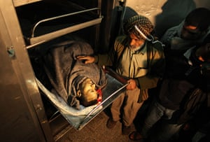 24 hours in pictures: Gaza Strip: People stand next to the body of a man killed in an explosion
