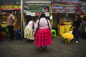 24 hours in pictures: Lima, Peru: An Andean woman stands in front of a stand at the Wishes Market