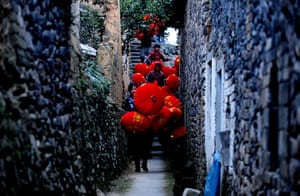 24 hours in pictures: Taizhou, China: Workers carry red lanterns from a workshop