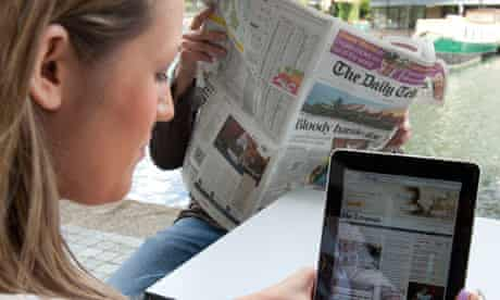 Woman and man reading Daily Telegraph in print and on an iPad
