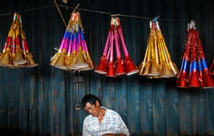 24 hours : Jakarta, Indonesia: A trader falls asleep as he sells paper trumpets