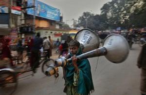 24 hours : Bodhgaya, India: An Indian worker carries a pair of loudspeakers