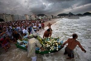 24 hours : Rio de Janeiro, Brazil: People push a boat as an offering for Yemanja