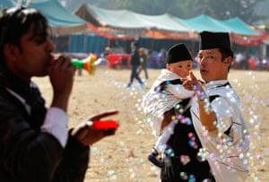 24 hours : Katmandu, Nepal: A man from the Gurung community shows his son soap bubbles