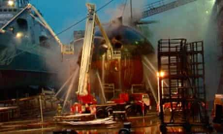 Firefighters spray water on the Yekaterinburg nuclear submarine