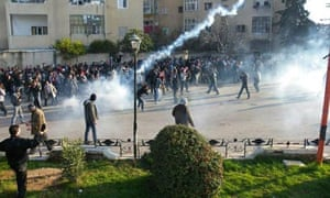 Protesters cover their faces from tear gas being fired in Adlb