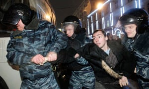 Russian riot police detain a protester in Moscow