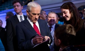 Ron Paul signs an autograph after a Republican presidential debate