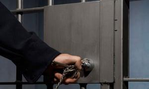 A guard unlocks a prison cell