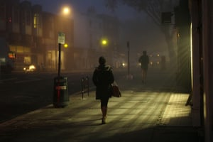 from the agencies: A woman and a jogger on a foggy Hampstead High Street in north London