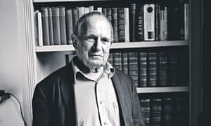 Christopher Logue in front of a bookcase